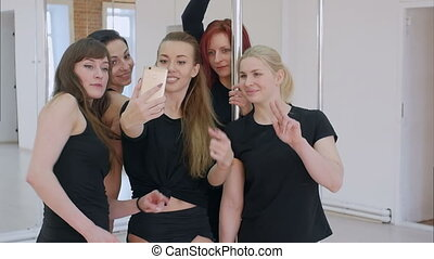 Group of beautiful young women taking a selfie with smartphone during a pole dance class