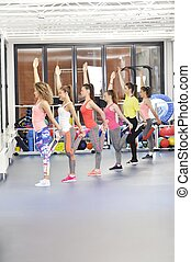 Group of beautiful young women working out at the gym
