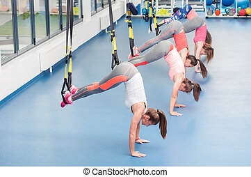 Group of beautiful young women working out on TRX.