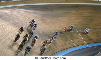 Group of bicyclists participates in competitions on bicycle track in sports complex