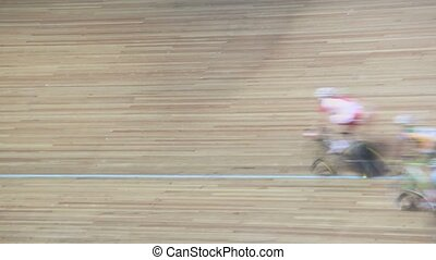 Group of bicyclists pass by track during race in gymnasium