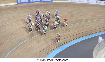 Group of bicyclists ride by track, shown in motion