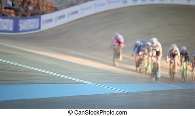 Group of bicyclists ride track during race, unfocused