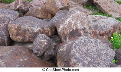 Group of big boulder stones lying in field, natural geologic...