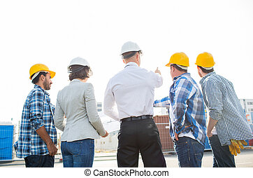 group of builders and architects at building site -...