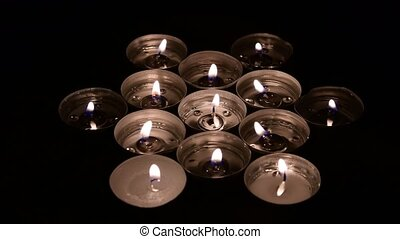 Group of burning tea light candles, rotating candles.