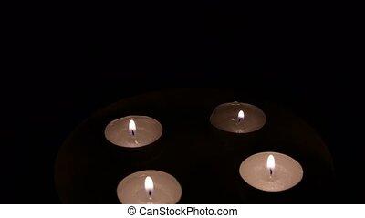 Group of burning tea light candles, rotating. Closeup. -...