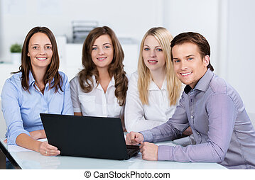 Group of business colleagues sharing a laptop