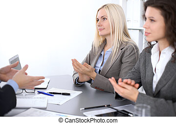Group of business people applauding at meeting  in office