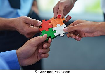 Group of business people assembling jigsaw puzzle and ...