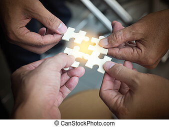 Group of business people assembling jigsaw puzzle wanting to put pieces of puzzle together on wood table backgroung for help support, teamwork concept