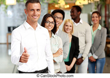 Group of business people giving thumb up to camera in the office