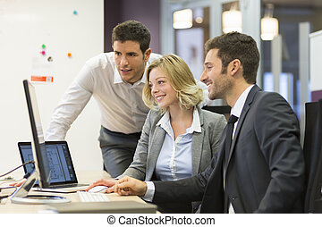Group of business people in a meeting at office, working on computer