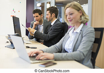 Group of business people in a modern office, working on computer