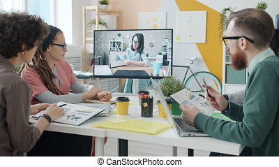 Group of business people listening to young woman through video conference meeting