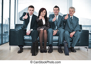 Group of business people sitting on sofa with thumbs up