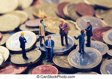 group of business people standing on euro money stack and talking