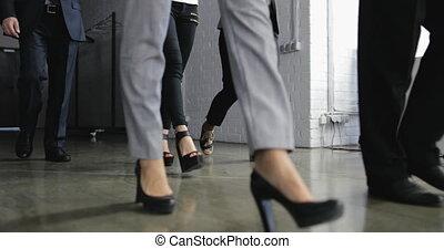 Group Of Business People Walking In Corridor Of Modern...