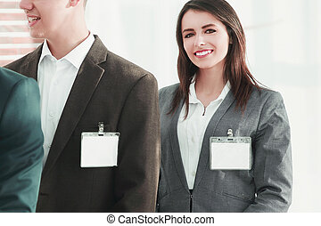 group of business people with blank badges on the background of the office