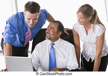 Group of business people working in office looking at laptop