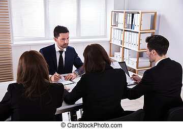 Group Of Businesspeople Discussing Paperwork