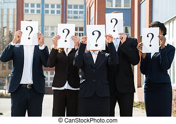 Businesspeople Hiding Face Behind Question Mark Sign