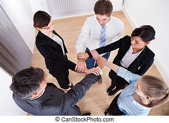 Group Of Businesspeople Holding Wrist