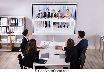 Group Of Businesspeople Looking At Projector