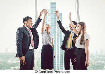 Group of businesspeople raising their hands