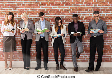 Group Of Businesspeople Reading Books