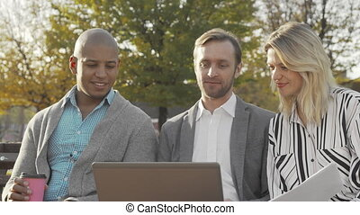 Group of businesspeople using laptop at the park