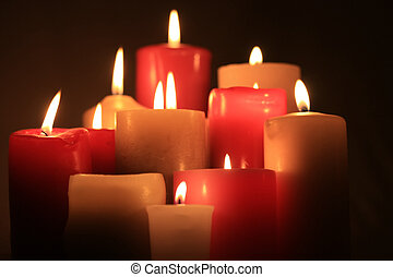 group of candles - A group of burning candles in red and ...