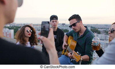 Group of carefree young friends dancing to the music played by guitar