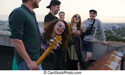 Group of carefree young friends smiling after dancing to the music played by guitar