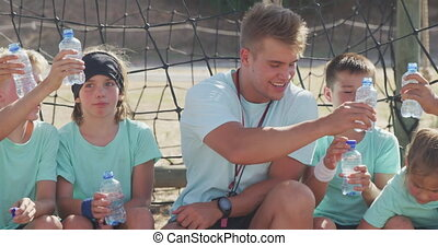Front view close up of a happy group of Caucasian boys and girls and a Caucasian male coach at boot camp together on a sunny day, taking a break, sitting together, drinking water, making a toast, all wearing green t shirts, in slow motion
