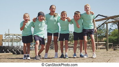 Front view of a happy group of Caucasian boys and girls at boot camp together on a sunny day, standing with arms around each other, looking to camera and shouting, all wearing green t shirts, in slow motion