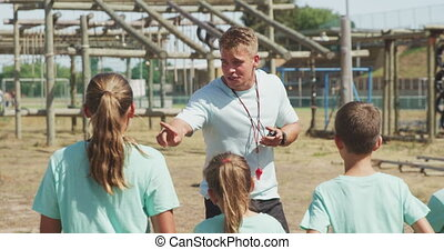 Side view of a happy group of Caucasian boys and girls and a Caucasian male coach at boot camp together on a sunny day, a coach is instructing the kids, all wearing green t shirts, in slow motion