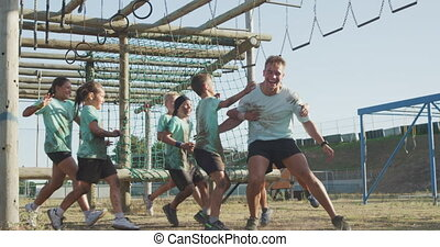 Side view of a happy group of Caucasian boys and girls and a Caucasian male coach at boot camp together on a sunny day, the kids are chasing the man, embracing, all wearing green t shirts, in slow motion