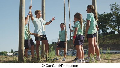 Side view of a happy group of Caucasian boys and girls and a Caucasian male coach at boot camp together on a sunny day, a man is holding ropes and instructing kids, all wearing green t shirts, in slow motion