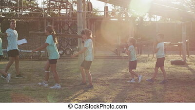 Side view of a happy group of Caucasian boys and girls and a Caucasian male coach at boot camp together on a sunny day, carrying wooden posts in pairs, all wearing green t shirts, in slow motion