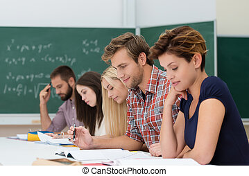 Mixed group of Caucasian determined students studying, looking at their notes at their desks in the class, with a chalkboard in the background