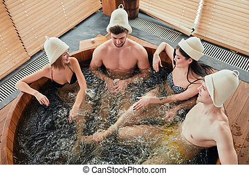 Two loving couple enjoying hot wooden whirlpool with warm water in modern bathhouse of a luxury hotel, view from above.