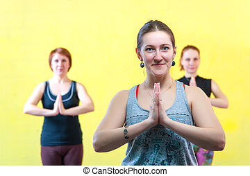 Group of caucasian women practicing yoga in class