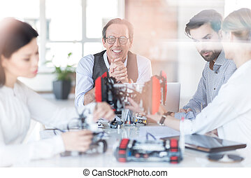 Group of cheerful engineers creating robot