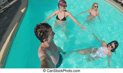 Group of cheerful friends making a selfie live session in social media in the pool water in their vacation