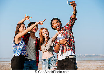 Group of cheerful friends taking selfie with mobile phone outdoors