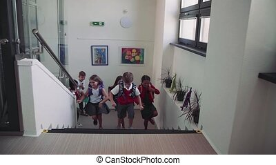 Group of cheerful small school kids running up the stairs...