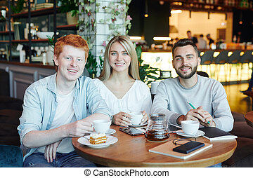 Group of cheerful students relaxing in cafe after classes and having tea
