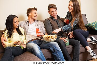 Group of cheerful students with drinks and popcorn in home interior