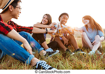 Group of cheerful young friendscelebrating with beer and soda outdoors